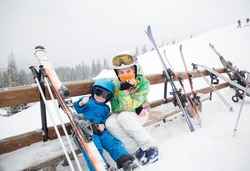 toddler boy and teenage girl ,brother and sister, are resting on bench, taking break from skiing in mountains. Winter sports for family. Children's skiing lesson at alpine school. Seasonal joys