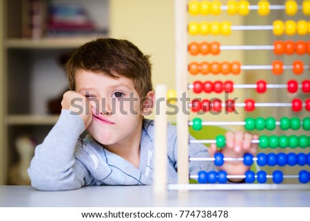 Toddler boy feeling bored and tired while playing with abacus at kindergarten. Hyperactive kid having attention deficit disorder