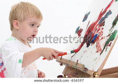 Toddler boy in big white shirt covered in paint at easel.  American blonde caucasian boy. Shot over white background.