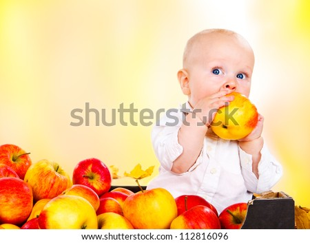 Toddler boy in white clothing eating red autumnal apples - stock photo