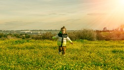 Toddler boy is running feeling alive and awake with his hands spreading wide like a plane in the meadow or park with yellow flowers early spring in Madrid at Valdebebas park
