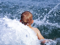Toddler boy jump in water. Splash of water around of child. Jumping playing in blue sea.