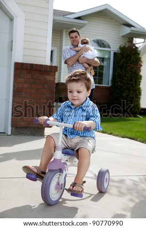 Toddler boy learning to ride tricycle with father in background