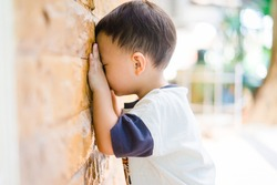Toddler boy playing hide and seek with friends in Kindergarten school.2.11 years old.School boy play hide and seek with friends in playground park at school.Little asian boy praying and crying.