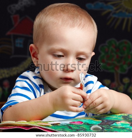 Toddler boy playing with a colorful felt book