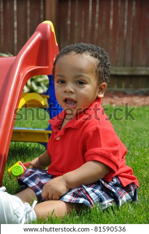 Toddler Boy sitting in grass Making a Face looking at Camera