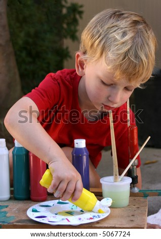toddler boy with brushes and colors painting