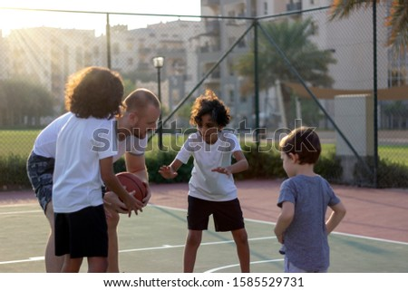 Toddler,brothers and their trainer playing basketball in park.Group of kids play basketball on playground on summer time.Happy family playing basketball together.Different age kids playing basketball