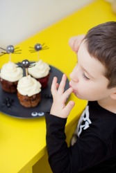 Toddler caucasian boy eats Halloween muffins or cupcakes with white cream and spiders decorations. Tasty and scary food on Halloween party