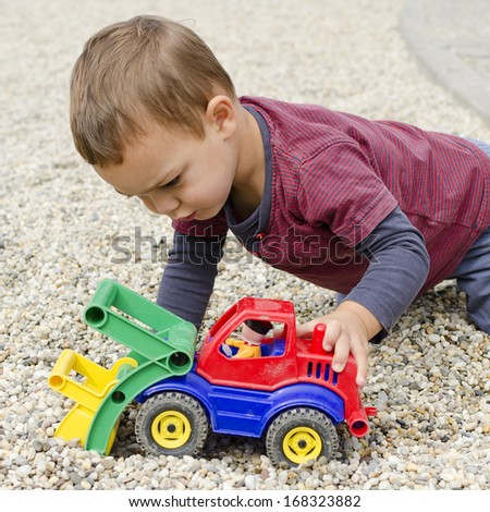 Toddler child boy playing with a plastic toy digger car.