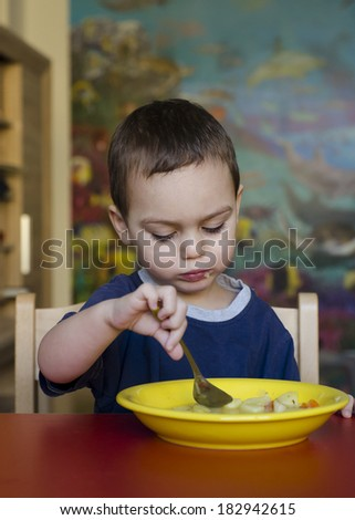 Toddler child eating soup at table at home or at kindergarten.