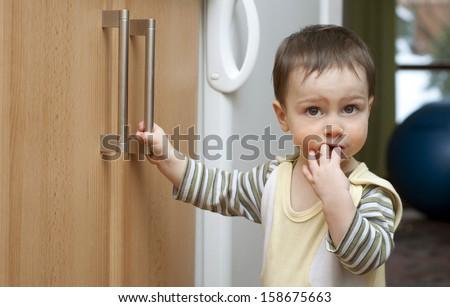 Toddler child in kitchen, children safety at home concept.