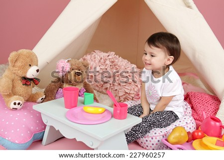 Toddler child, kid, engaged in pretend play with food, stuffed toys, and teepee tent