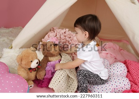 Toddler child, kid, engaged in pretend play with stuffed toys, and teepee tent