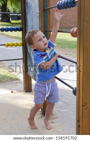 Toddler child playing in playground with big abacus.