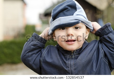 Toddler child playing outside trying to put on his hat.