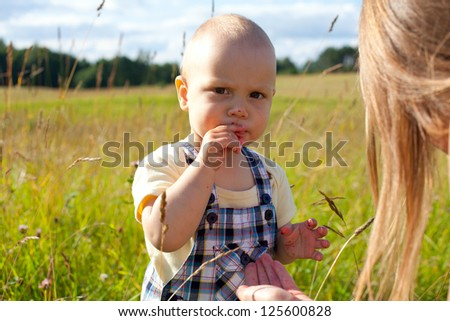 toddler eating berries on summer field