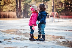 toddler girl and boy kisses on the early spring walk with paper boats in hands
