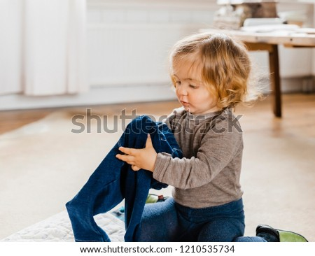 Toddler girl getting dressed in living room - Hindeloopen, Friesland, Netherlands