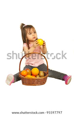 Toddler girl giving apple from a basket with different fruits isolated on white background