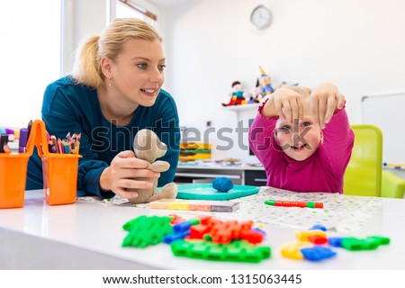 Toddler girl in child occupational therapy session doing sensory playful exercises with her therapist.  #1315063445