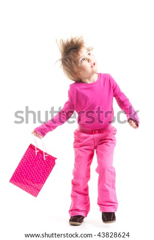 Toddler girl in pick outfit holding gift bag