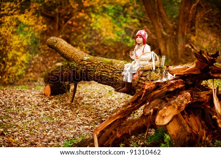 Toddler girl in red hat sitting on huge tree in forest and havin