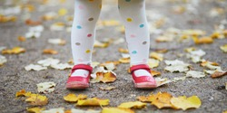 Toddler girl in red shoes and polka dot pantihose standing on fallen leaves in a fall day. Child enjoying autumn day in park. Stylish and beautiful clothes for kids