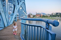 Toddler girl in white dress and pink shoes walks along blue metal railing on the Market Street Bridge at dusk in Chattanooga Tennessee. Waterfront district in background. Taken on July 11th 2014.
