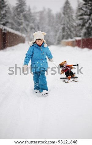 Toddler girl is giving a ride to a toy bear on her snow scooter