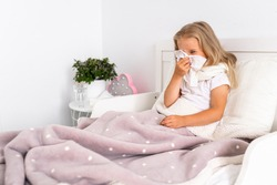 Toddler girl is lying in bed. The child is cold and sick and has a runny nose and snot. The child wipes his nose with a napkin. Allergy, flu