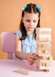 Toddler girl is playing Tumble tower wooden block game. Wooden tower game