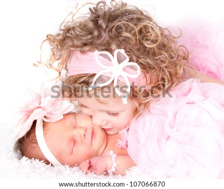 Toddler girl kissing her sleeping baby/infant sister