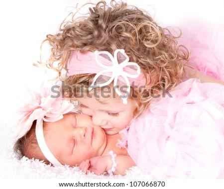 Toddler girl kissing her sleeping baby/infant sister