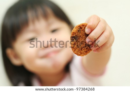 Toddler girl offering you a chocolate chip cookie
