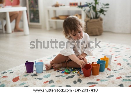 Toddler girl plays with beads and multicolored buckets, the development of fine motor skills and sensory development, the study of colors. Self-study of the child and Montessori method ストックフォト ©
