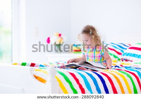 Toddler girl reading a book in bed. Children read books. Kids learning. Preschool kid doing homework in bedroom. Colorful textile bedding for child and baby room. Preschoolers learn and study at home