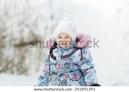 44bf3a559ef2 Toddler girl s portrait in white knitted hat and blue warm winter ...
