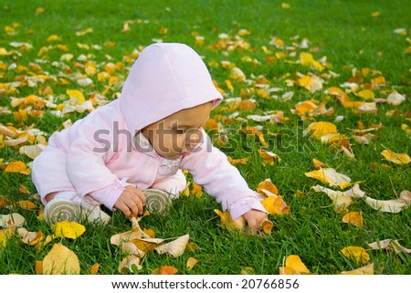 Toddler girl sitting in the park on green grass