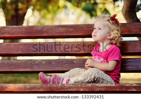 toddler girl sitting on  the bench