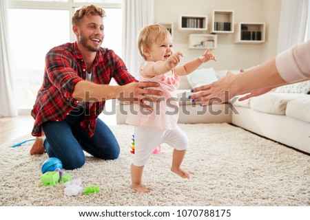 Toddler girl walking from dad to mumÕs arms in sitting room