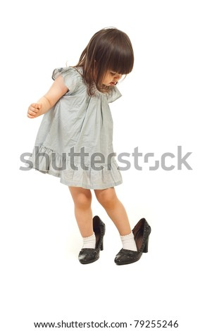 Toddler girl wearing big shoes and looking down with attentive face isolated on white background