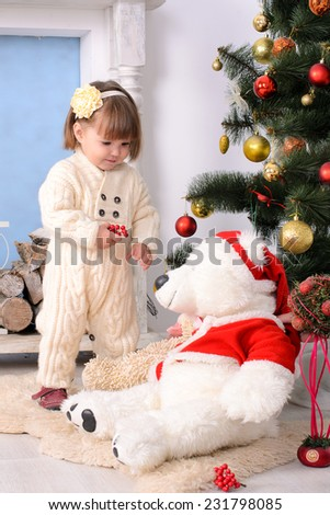 toddler girl with big teddy bear at christmas tree indoors
