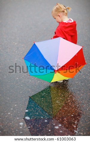 Toddler girl with colorful umbrella, beautiful reflection on wet ground