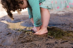 Toddler girl with curly hair and pink and green polka dot skirt playing barefoot in sand and water.