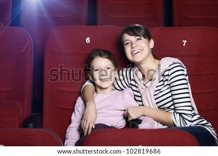 Toddler girl with mother in the movie theatre