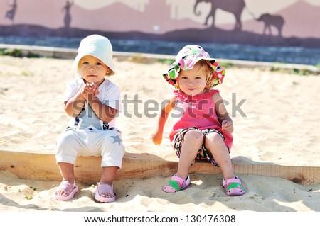 toddler girls playing in sand