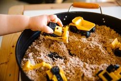Toddler hand holding bulldozer above construction sensory tray with cloud dough  Selective focus.