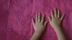 Toddler hands on crumpled tissue paper on table. Directly above view of magenta wrinkled paper and kid palms of hands touch uneven pink paper texture