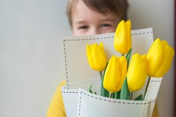 Toddler happy and smiling boy with a large bouquet of yellow tulips in Mothers Day. Portrait of a beautiful little kid on a gray background. Spring background